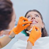 Woman having her teeth examined at dentist office. Female dentist choosing the right color of teeth
